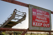 Close-up View Of An Improvised Keep Out Sign Attached To A Rusting Farm Gate Entrance. In View Is A Vintage Bailing Machine In The Background.