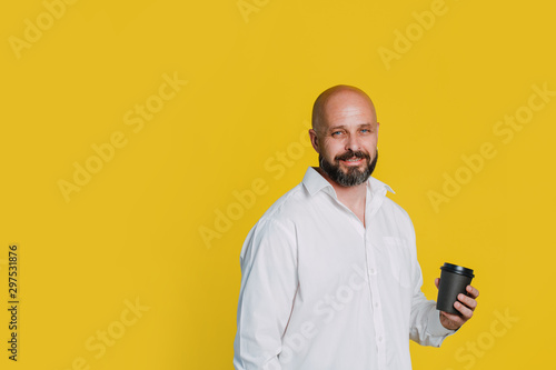 Handsome serious middle aged man in a white shirt smiles and holds a glass of coffee against yellow background with copy space - 297531876