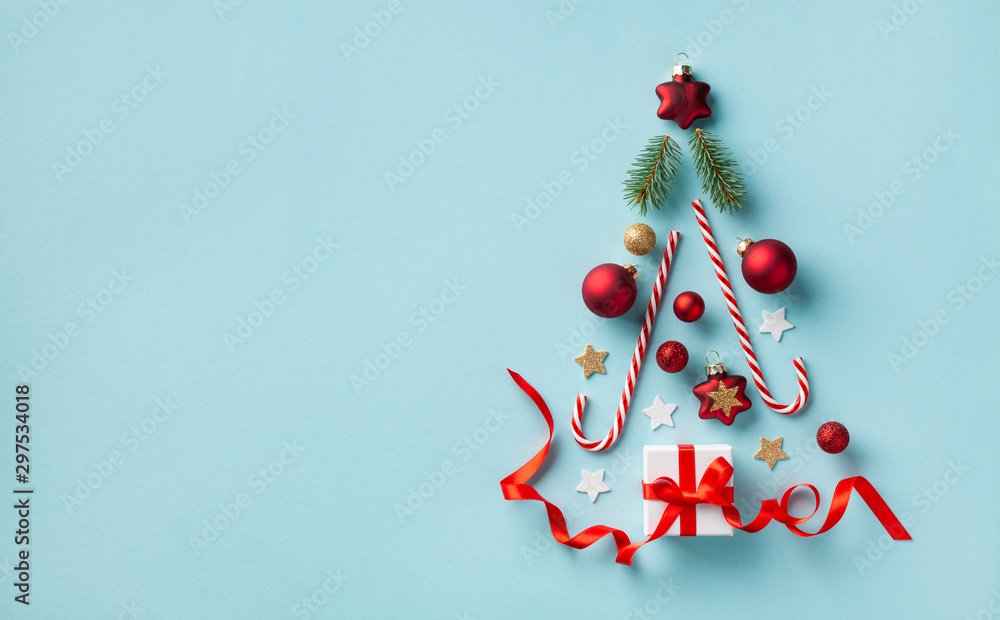 Fototapeta Creative Christmas fir tree made of gift box and holiday decorations on blue background top view. New Year greeting card. Flat lay.