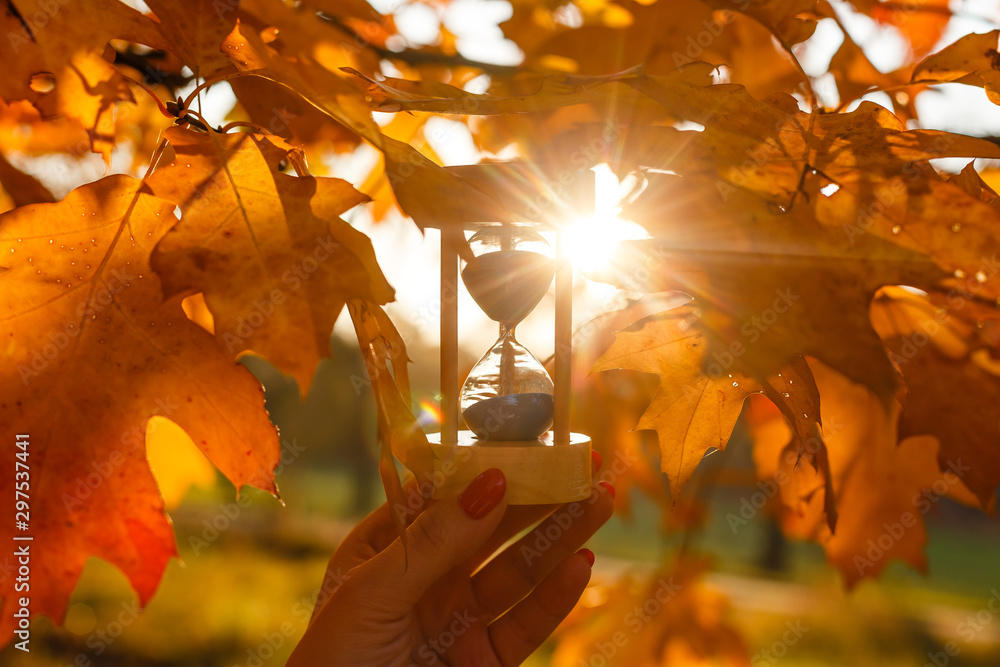 Fototapety, obrazy: Autumn time theme, Sandglass on fallen leaves in various colors with copy space.