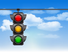 Traffic Lights With All Three Colors On Hanging Against Blue Sky