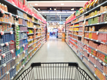 Supermarket Aisle With Empty Shopping Cart With Customer Defocus Background