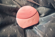 Top View Of Pink Silicone Cleansing Facial Brush. Facial Cleansing Device