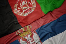 Waving Colorful Flag Of Serbia And National Flag Of Afghanistan.