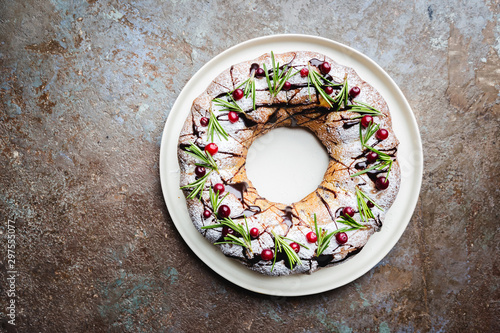 Fotografering Cranberries bundt cake with chocolate and orange on a white plate