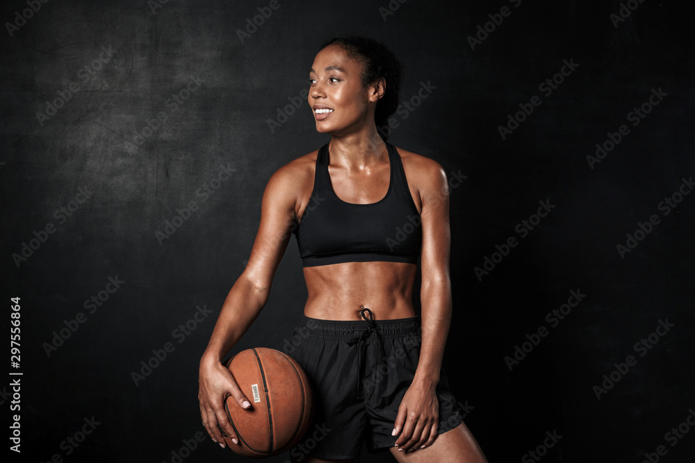 Fototapety, obrazy: Image of smiling african american woman in sportswear holding basketball