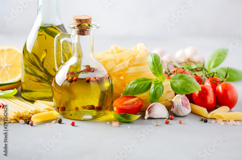 Fototapeta Italian food ingredients – pasta, tomatoes, basil and olive oil on gray concrete background. obraz