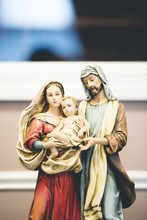 Vertical Shot Of Mother Mary Figurine With A Blurred Background