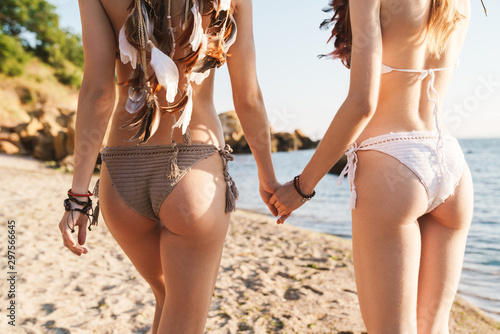 Image of beautiful hippy girls in swimsuits walking by seaside in morning Canvas Print