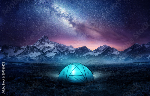 Fototapeta Camping in the mountains under the stars. A tent pitched up and glowing under the milky way. Photo composite. obraz