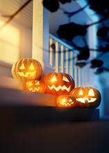 Halloween Pumpkin Jack O' Lanterns Lighting Up A Decorated Front Porch. 3d Illustration.