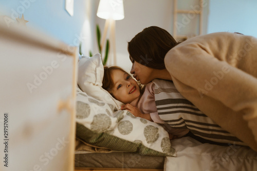 Photo Mother kisses her daughter before bedtime