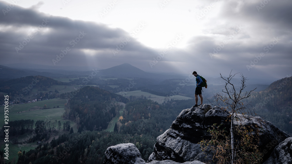 Fototapety, obrazy:   Man silhouette stay on sharp rock peak. Satisfy hiker enjoy view. Tall man on rocky cliff watching down to landscape. Sun breaking through after a storm on an autumn afternoon