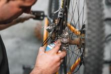 Mechanic Man Hands, Spraying Oil To A Bike Chain. Bicycle Maintenance .