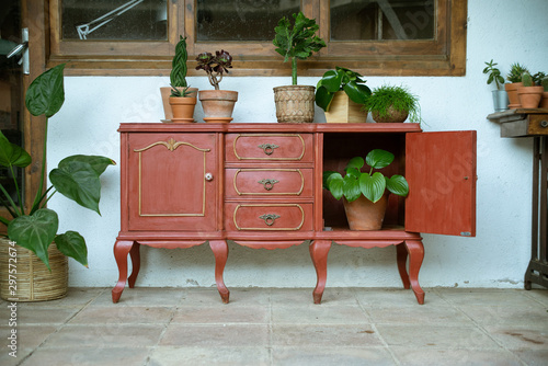Photo Aparador vintage / mueble antiguo con plantas en patio exterior con ventana