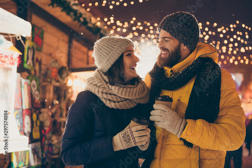 Photo of two people cute couple husband guy wife lady drink hot beverage x-mas eve spend time magic land newyear shopping market buying gifts wear coats outside