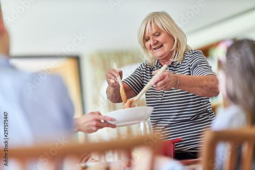 Großmutter verteilt Spaghetti auf Teller Canvas Print