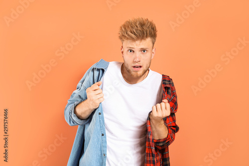 Valokuva  Portrait of surprised man wearing different shirts on color background