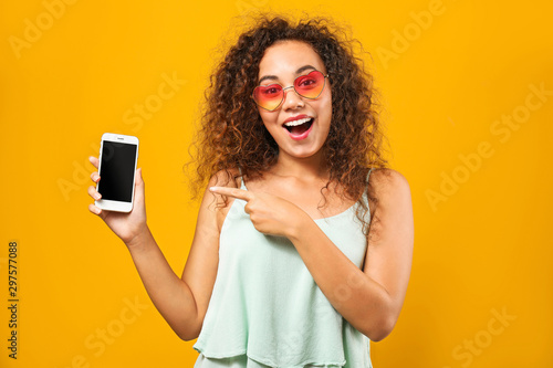 Leinwand Poster  Portrait of happy African-American woman with mobile phone on color background
