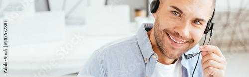 Fotografía panoramic shot of happy operator in brokers agency touching headset and looking