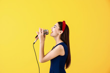 Beautiful Young Female Singer With Microphone On Color Background