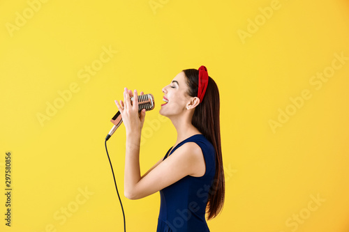 Beautiful young female singer with microphone on color background - 297580856