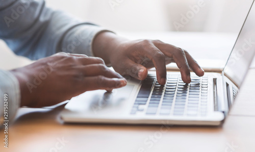 Fotografía Unrecognizable african american man typing on laptop keyboard in office
