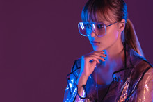 Fashion Sexy Young Woman Girl Model Attractive Face Wearing Stylish Trendy Transparent Raincoat Eyewear Sunglasses Looking Away Posing In Neon Light At Purple Magenta Studio Background Copy Space