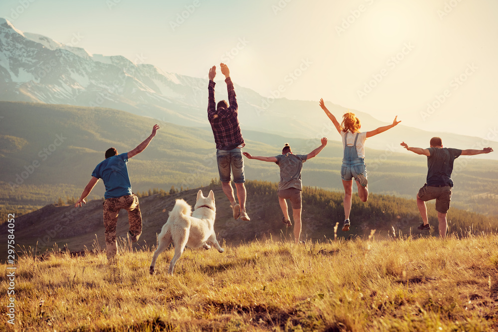 Fototapeta Group of friends runs and jumps in mountains