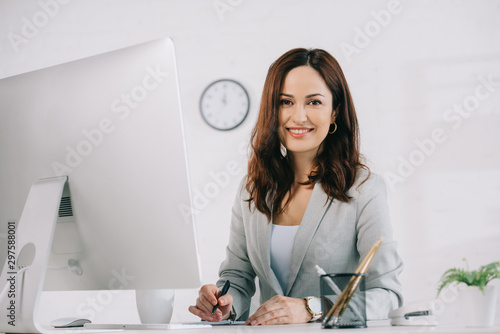 Photo beautiful, smiling secretary looking at camera while sitting at workplace near c