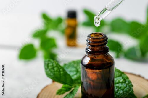 Fototapeta mint essential oil drop falling from dropper into the bottle