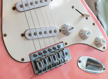 Close Up Of An Old Style Pink Electric Guitar.  Details Of Rock Guitar. Strings And Volume Control. Part Of Modern Electric Six String Guitar Pink Color With Glossy Finish.