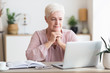 Old woman reading article online, using laptop