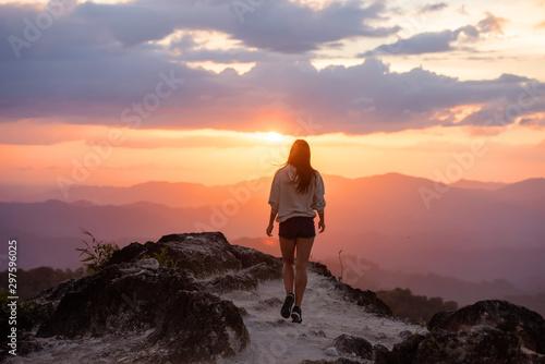 Slim beautiful girl walks mountains at sunset - 297596025