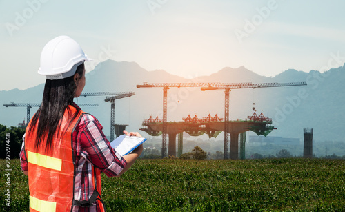 Fototapety, obrazy: The back view of a female engineer wearing a reflective jacket and a helmet is being inspected at the bridge construction site.