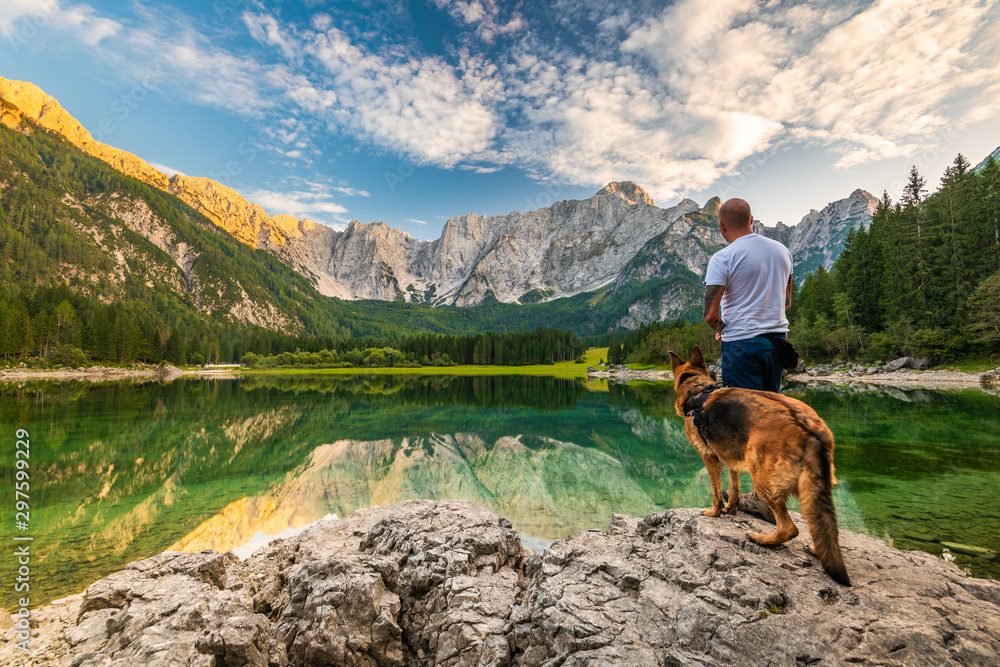 Fototapety, obrazy: Tattoed Man with Dog Looking at Beautiful Lake and Mountains. Outdoor Active  Lifestyle
