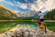 Tattoed Man With Dog Looking At Beautiful Lake And Mountains. Outdoor Active  Lifestyle
