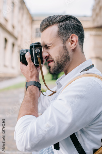 side view of bearded man taking photo on digital camera Wall mural