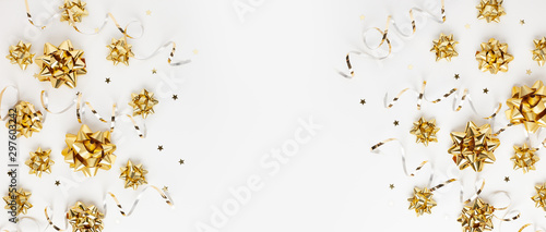 Obraz Christmas or New Year composition with gold sparkling ribbon decorations on white background. Flat lay, copy space. - fototapety do salonu