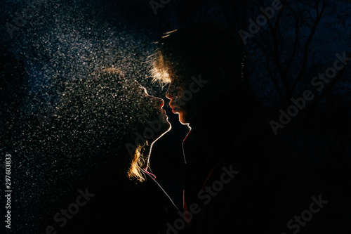 Canvas Print Loving couple silhouette. Back light and spray.