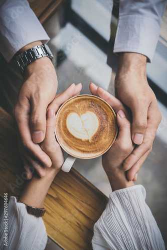 Valentine day, Top view of a young lovers hand holding a heart shaped coffee cup on a wooden table in the coffee shop. - 297604646