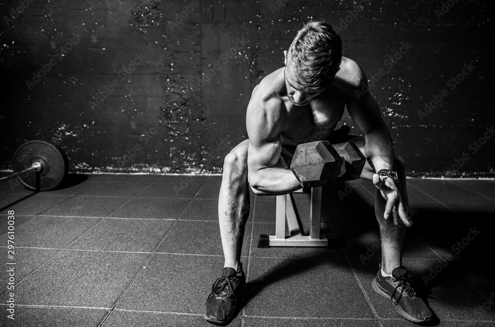 Fototapety, obrazy: Young strong muscular sweaty fit man biceps muscle workout cross training with heavy dumbbell in the gym dark image with shadows real people black and white