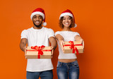 Friendly african man and woman reaching Christmas gifts to camera