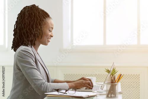 Fotografie, Obraz  African American Woman Working On Laptop In Office, Side View