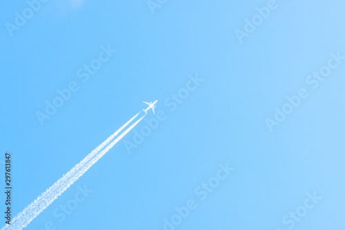 Airplane in a blue sky with clouds and condensation trails, Germany Canvas Print