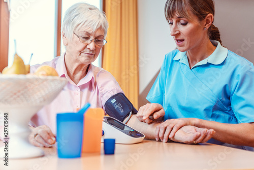 Obraz na plátně Nurse measuring blood pressure on senior woman