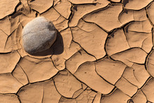Cracked Mud Around Smooth Stone In Dry Riverbed
