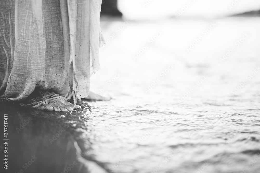 Fototapety, obrazy: Closeup shot of a person wearing a biblical robe while standing on the shore in black and white