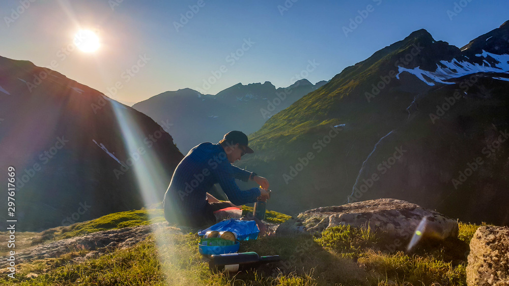 Fototapety, obrazy: A young man cooking a dinner in the wilderness during the sunrise. He is sitting at the edge of a mountain, mixing the dish. He is surrounded by tall mountains. Alpine camping. Outdoor kitchen.