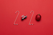 Christmas And New Year Holiday 2020 Inscription From Various Decorated Objects Classic Red Glass Baubles Ball, Toy Car On A Red Background.